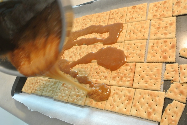 Pouring the toffee over the saltines.