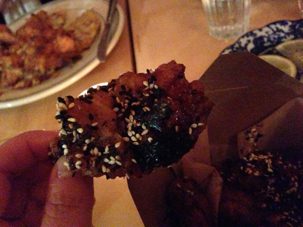 A close up of the double fried chicken wing coated in nori and black and white sesame seeds!