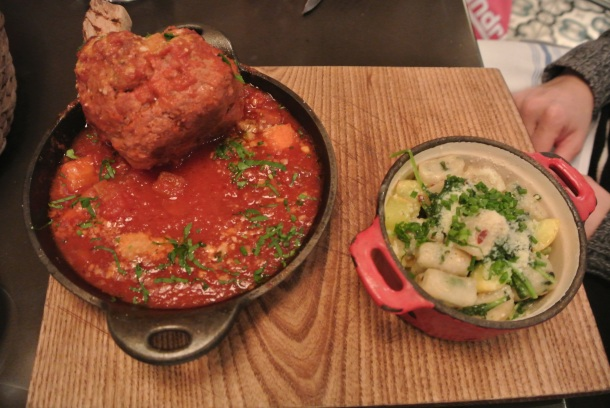 Veal meatball tomahawk with braised tomatoes and gnocchi.