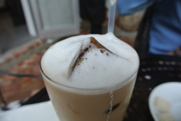 A close up view of the coffee ice cube in the iced cafe con leche.