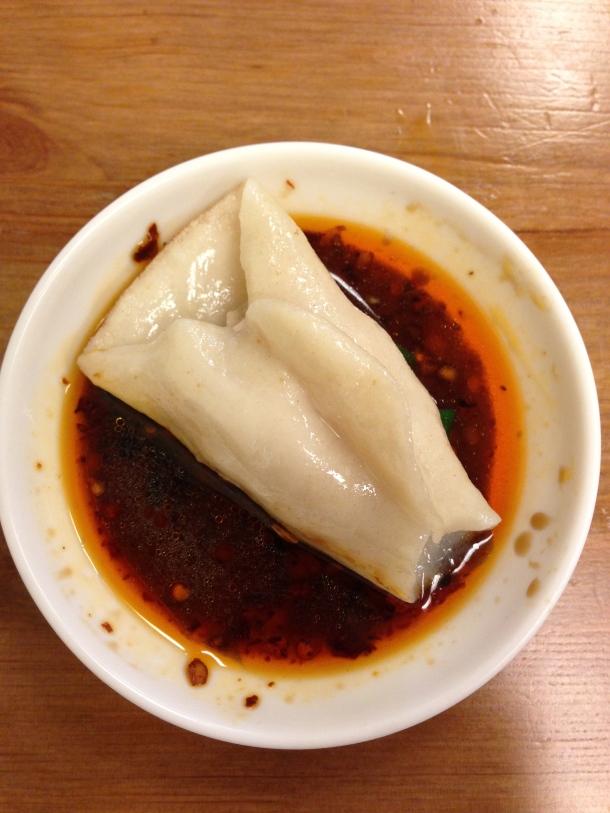 Dipping the dumpling in hot sauce.