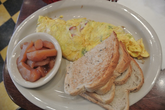 The Lorraine omelette made with spinach, bacon, tomatoes and swiss cheese with a side or rye toast and fried apples.
