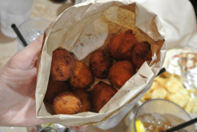 The famous Rusty Belly hush puppies served in a paper bag.