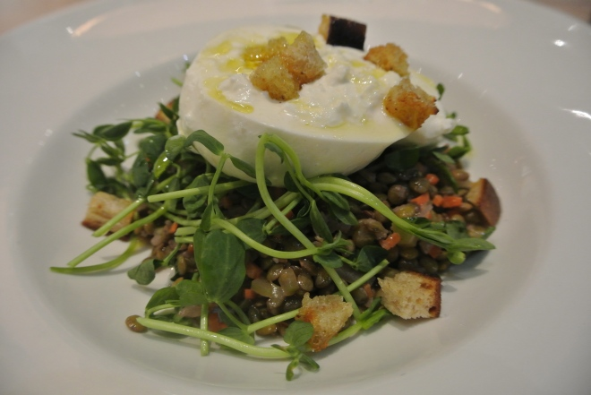 A burrata appetizer with lentils, pea shoots, croutons and vin cotto.