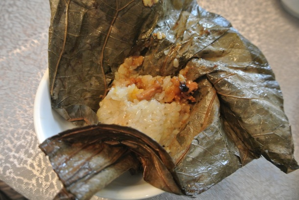Sticky rice with conpoy and chicken in lotus leaf parcel.