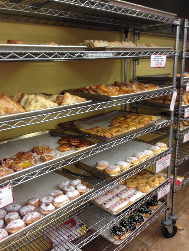 Racks of donuts and fruit turnovers.